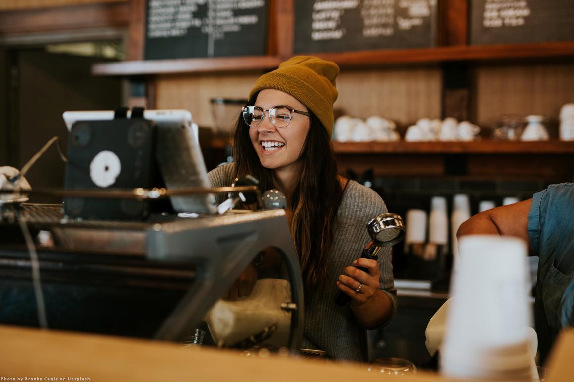Foto van een lachende vrouw achter een espressomachine. De foto werd gemaakt door Brooke Cagle op Unsplash.
