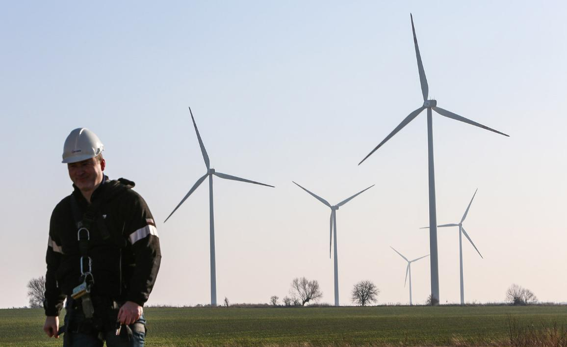 An employee passes by wind turbines at the Golice Wind Park in Poland
