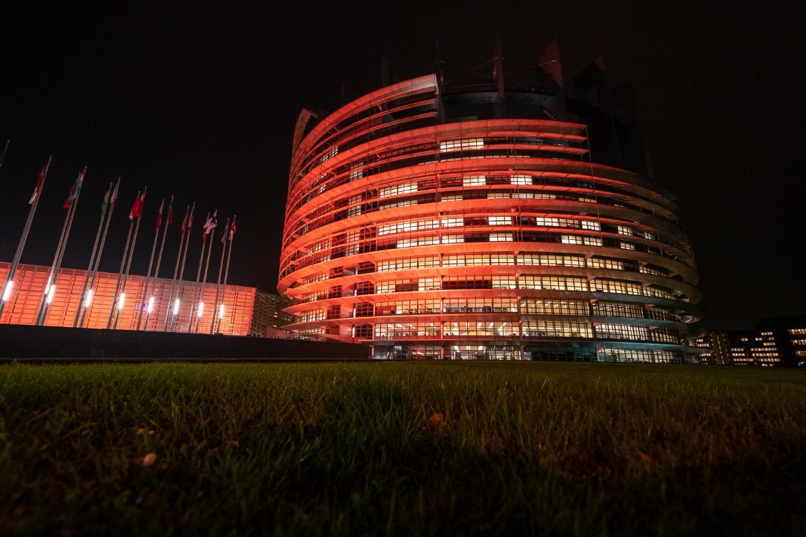 The Parliament's building in Strasbourg lit in orange colour_
