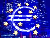 Euro sign in front of buildings in the night