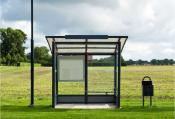 A bus stop is depicted standing in front of a field. Dark clouds indicate a storm is coming. There is no one viewable in the image.