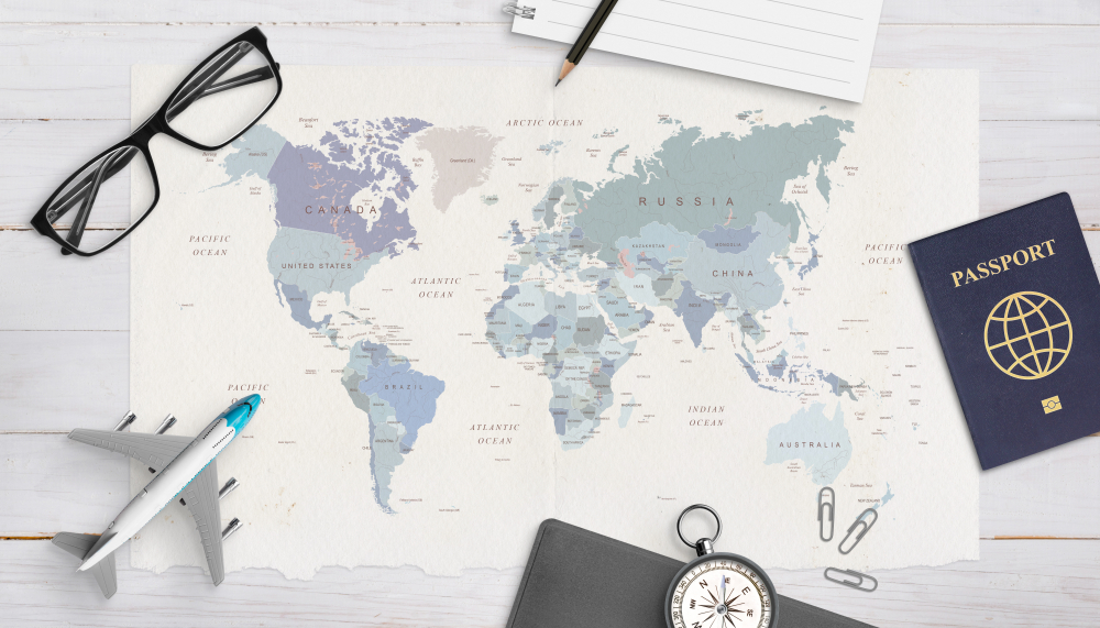 Concept of travel organization. Airplane model, passport, compass, glasses, pad and pencil on world map.