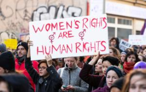 Demonstration in Berlin, Germany, March 8 2019. The demonstrators are holding a sign that reads Women's Rights are Human Rights in red. Graffiti in the background.