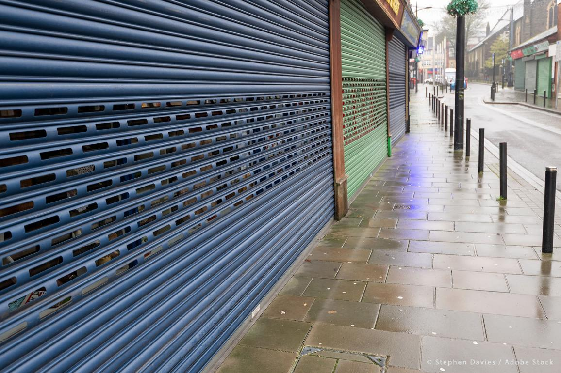 High Street Shops closing down with shutters closed, decline in shopping in Wales