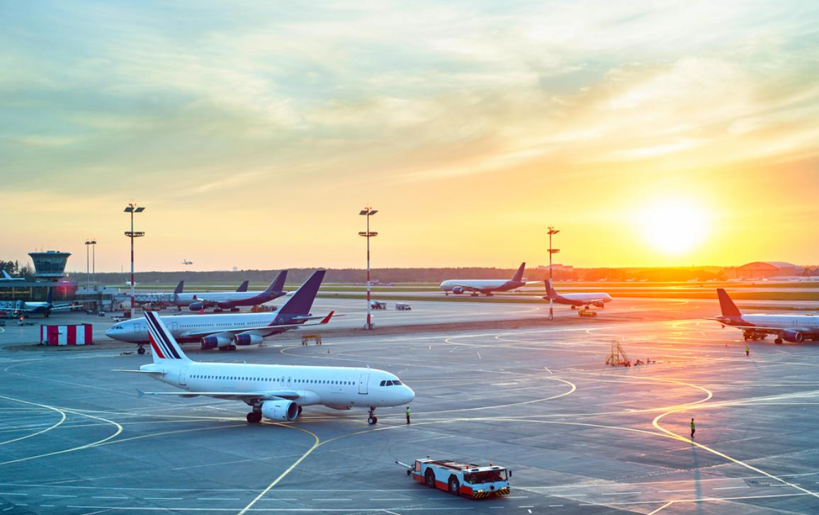 Airport with many airplanes at beautiful sunset