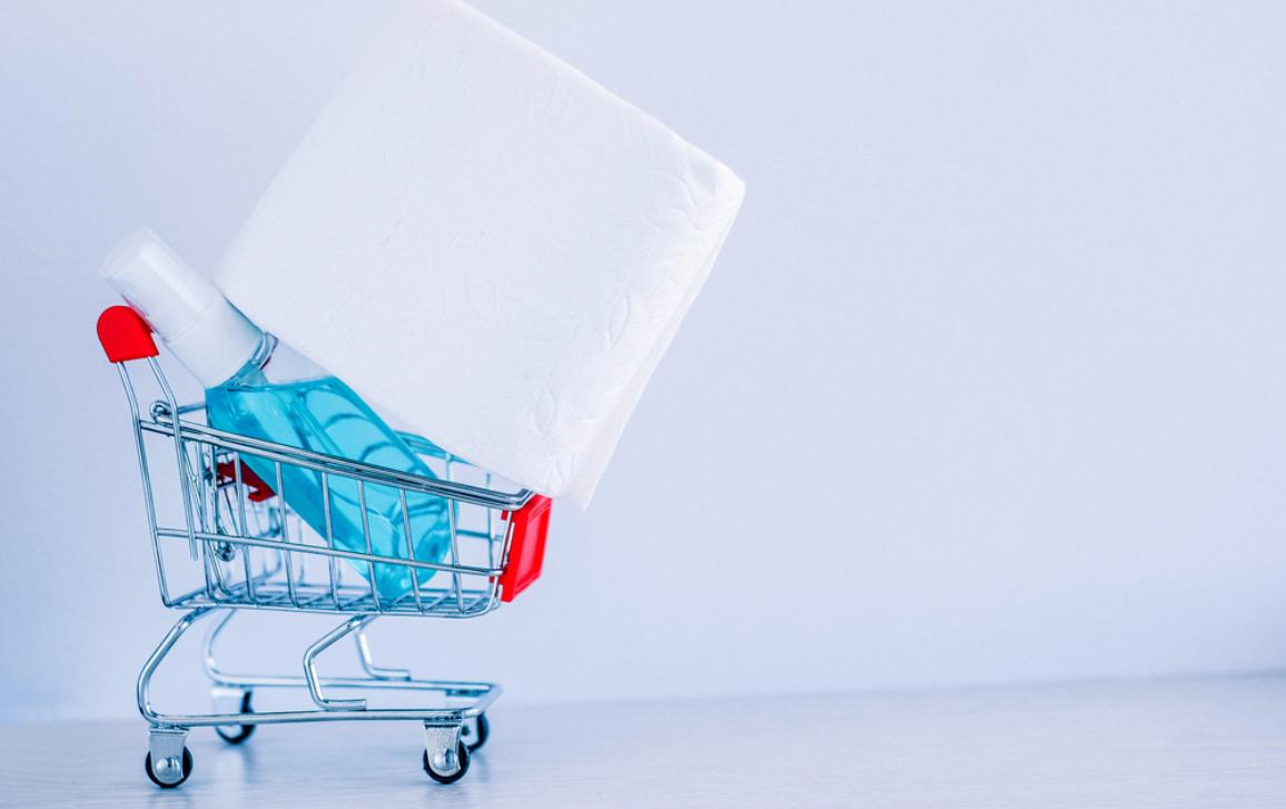 a roll of toilet paper and a sanitizer in a shopping cart