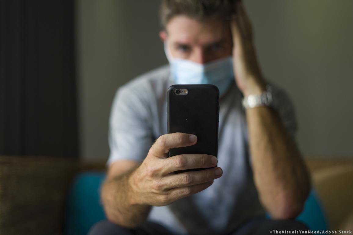 Medium shot van man met mondmasker die met zijn hand aan zijn hoofd op zijn mobiele telefoon kijkt  ©TheVisualsYouNeed/AdobeStock
