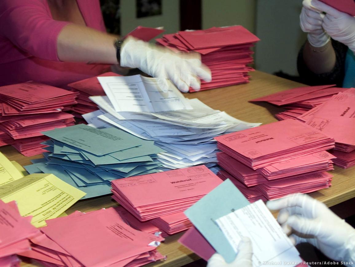 Imagen de la apertura de votos por correo en la que se ven distintas pilas de sobres de colores y papeletas y a trabajadores electorales con guantes y mascarillas. ©Michael Dalder/Reuters/Adobe Stock