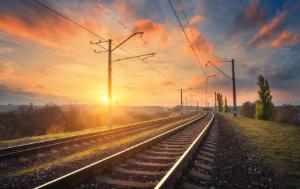 Railway against beautiful sky at sunset. Industrial landscape with railroad, colorful blue sky with red clouds, sun, trees and green grass. Evening in autumn
