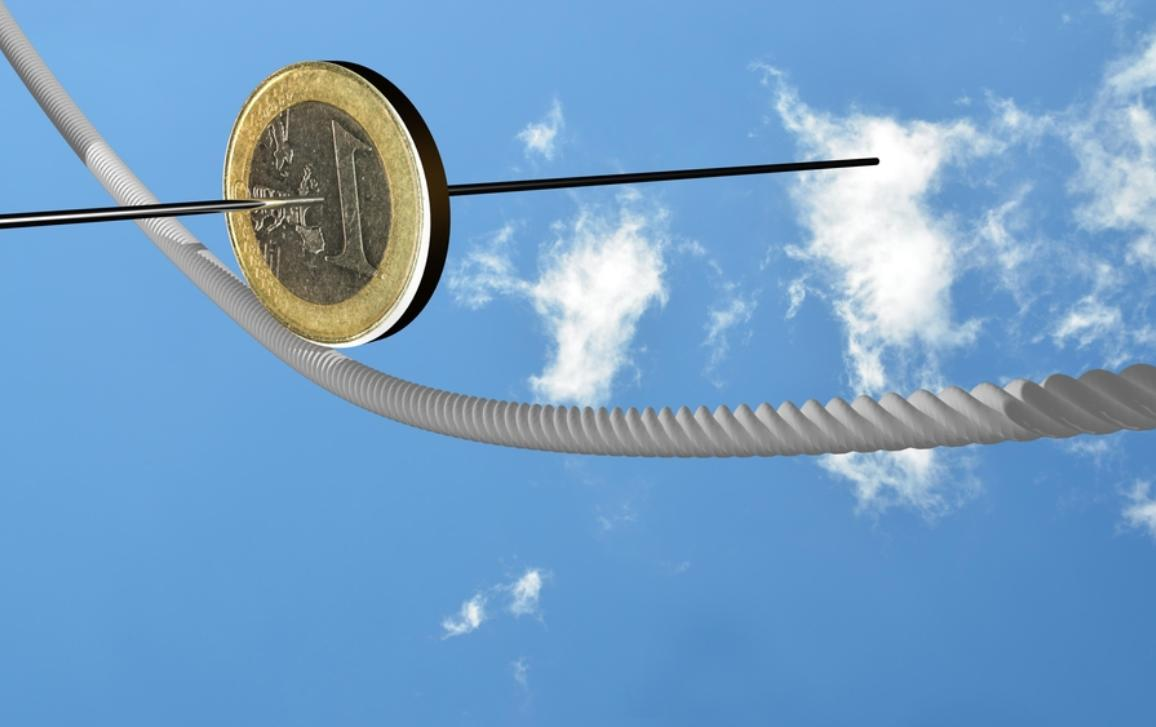1 Euro coin balancing on a cord
