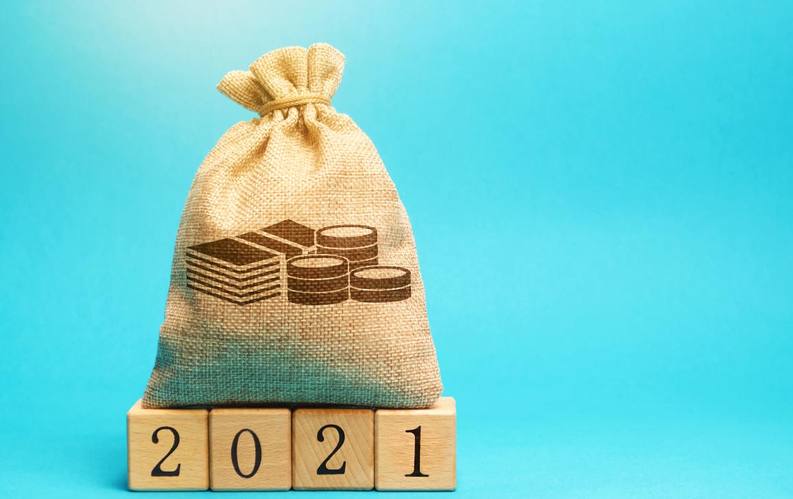 Bag of cash on top of blocks spelling '2021'