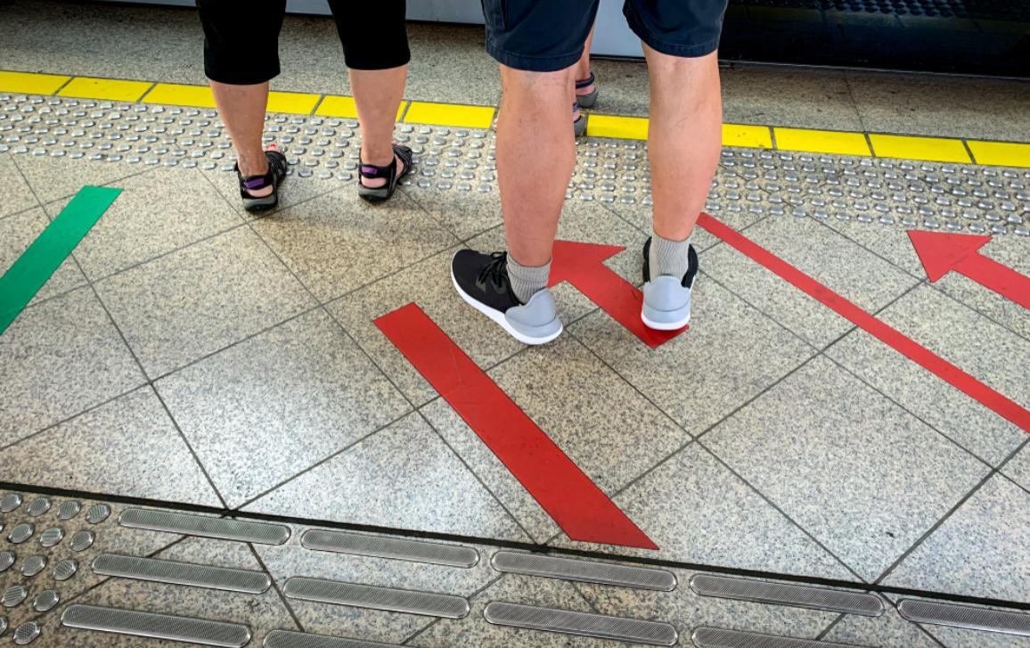 Passenger standing at railway platform waiting for board the high speed electric train at subway station. Modern train transport. Tourist standing at floor paint red arrow sign. Urban travel lifestyle