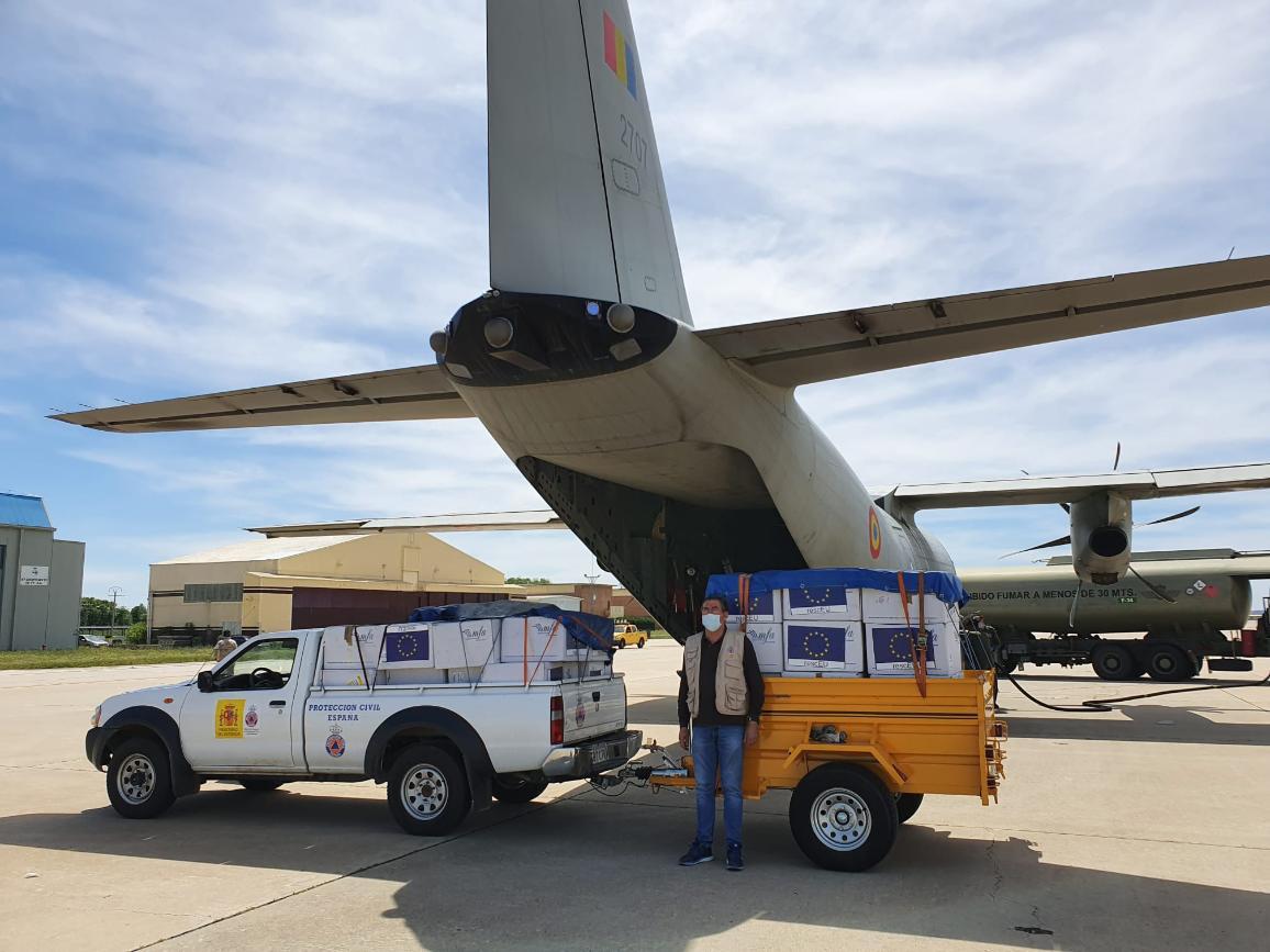 Vliegveld met vrachtvliegtuig, pick-up truck met dozen met EU-logo