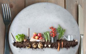 miniature vegetable garden presented on a plate with knife and fork