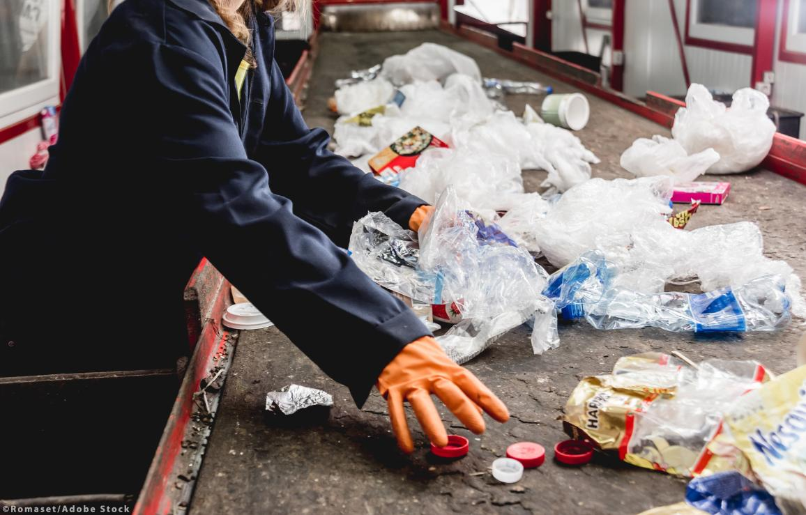 At modern recycling plant a workers sorting trash to be processed. ©Romaset/AdobeStock