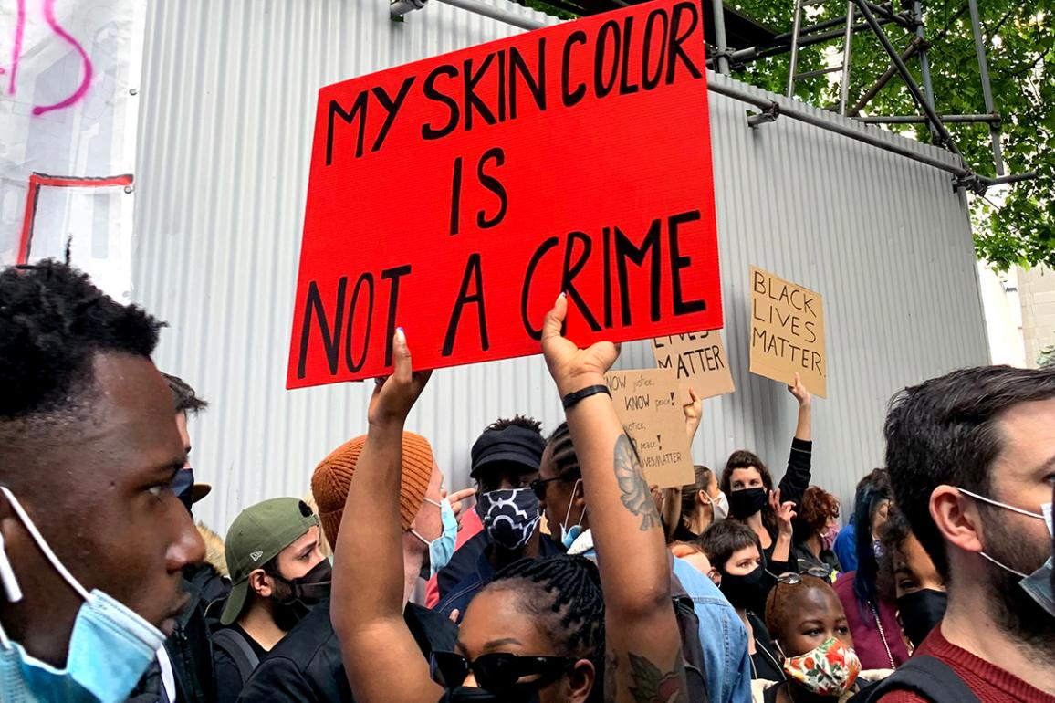 "A Black lives matter protest in the street with the sign ""My skin color is not a crime"""