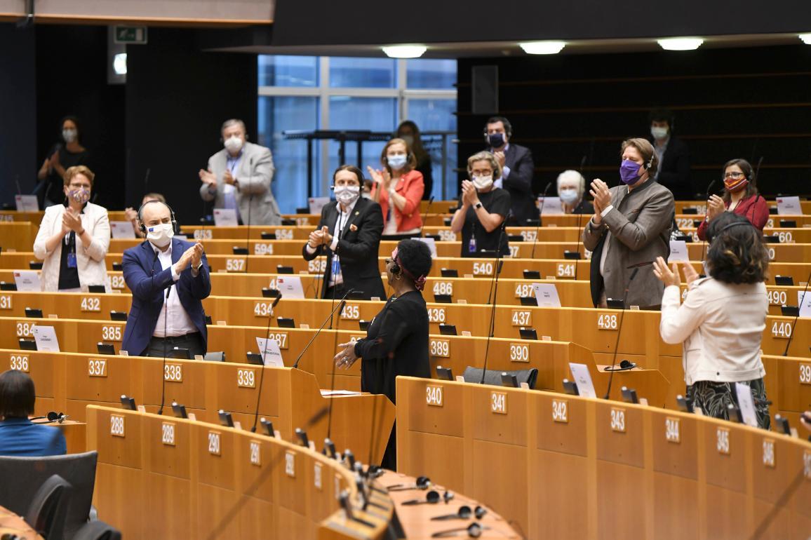 Poslanci stoja a tlieskajú v plenárnej miestnosti