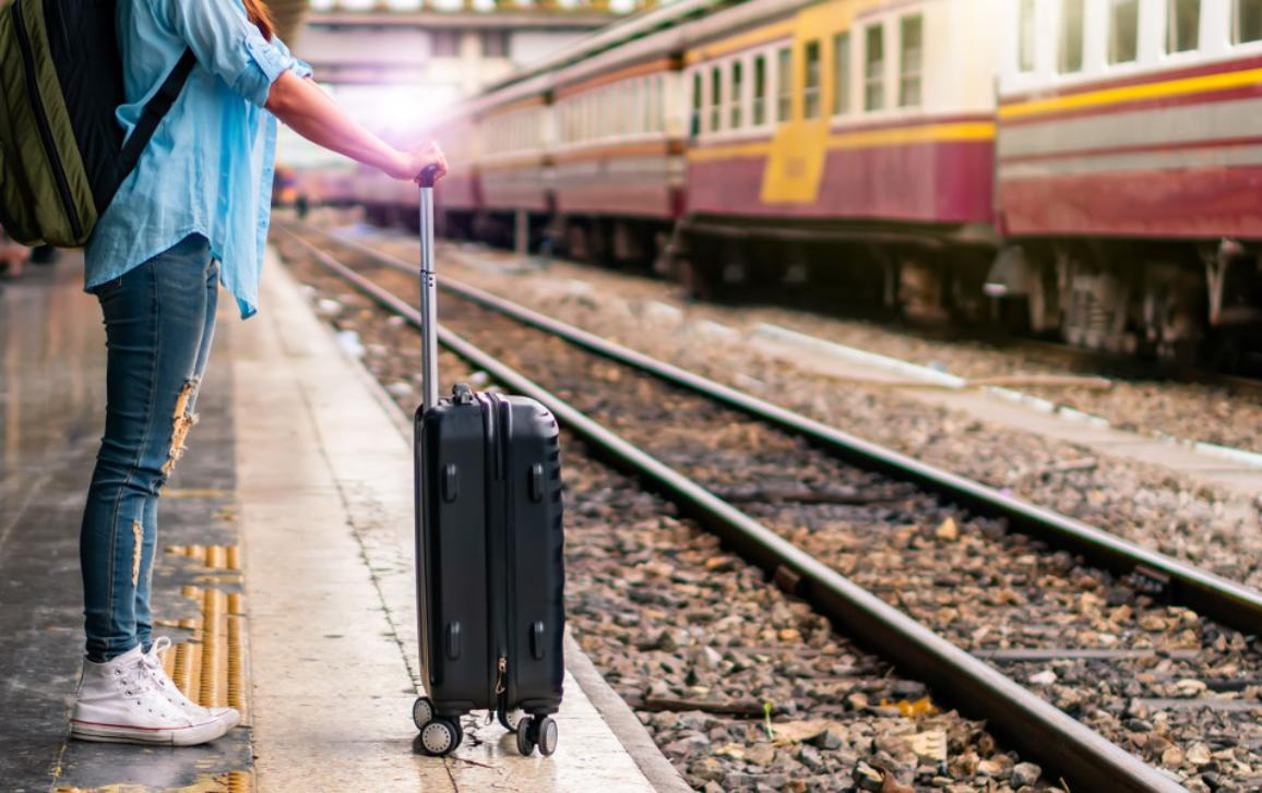 Solo backpacker traveler plan safety trip low cost budget summer holiday after coronavirus crisis. Empty tourist on train railway platform.
