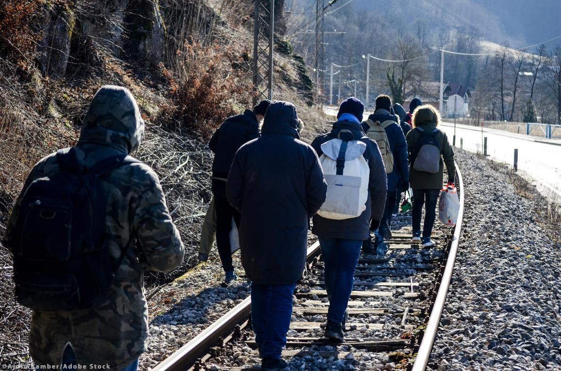 Group of migrants walking along railway tracks. ©Ajdin Kamber/AdobeStock
