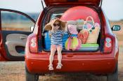 Little girl in straw hat sitting in the trunk of a car stuffed with holiday equipment