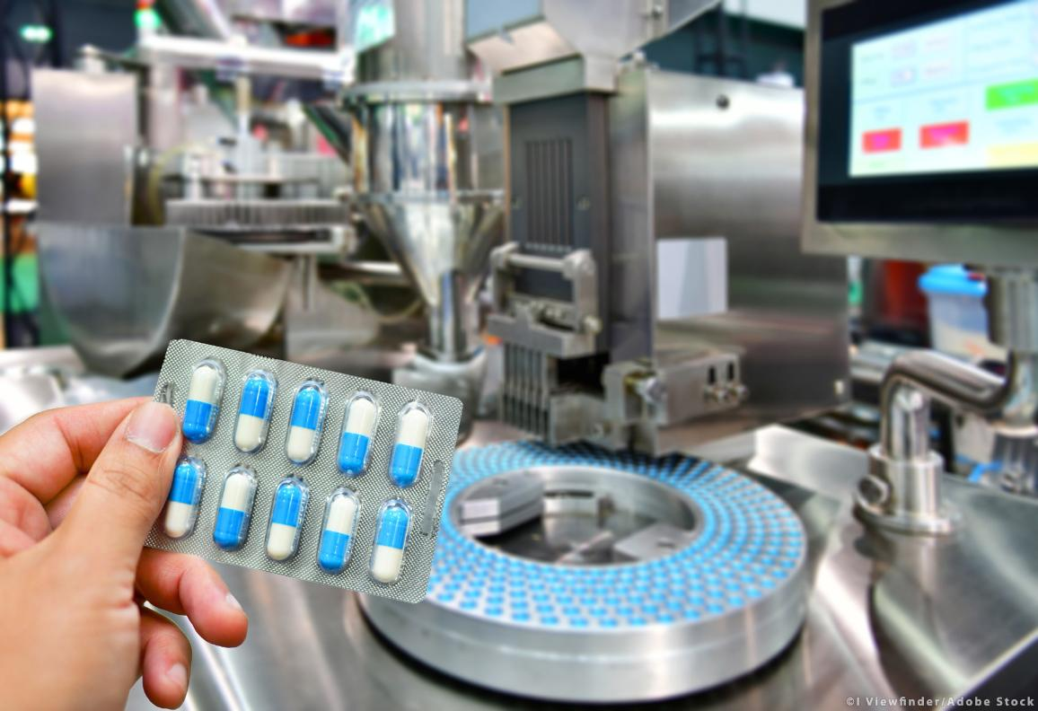 Hand holding blue capsule pack at a medicine pill production line. ©I Viewfinder/AdobeStock