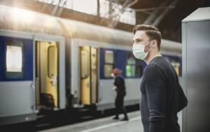 Man with flu mask on train station