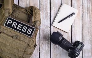 Journalist's tools put on a desk: ´camera, blocknote with pen and bulletproof vest