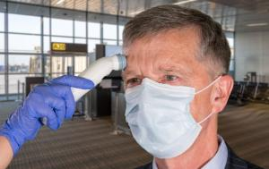 At the airport terminal an adult wearing mask having a temperature test taken to check coronavirus status