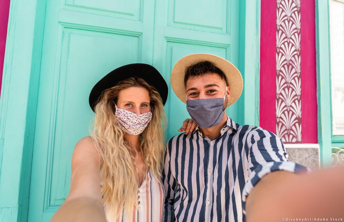 Nella foto, una coppia fa un selfie in viaggio, indossando le mascherine ©DisobeyArt/Adobe Stock