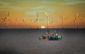 Fishing boat and wind turbines at the sunset