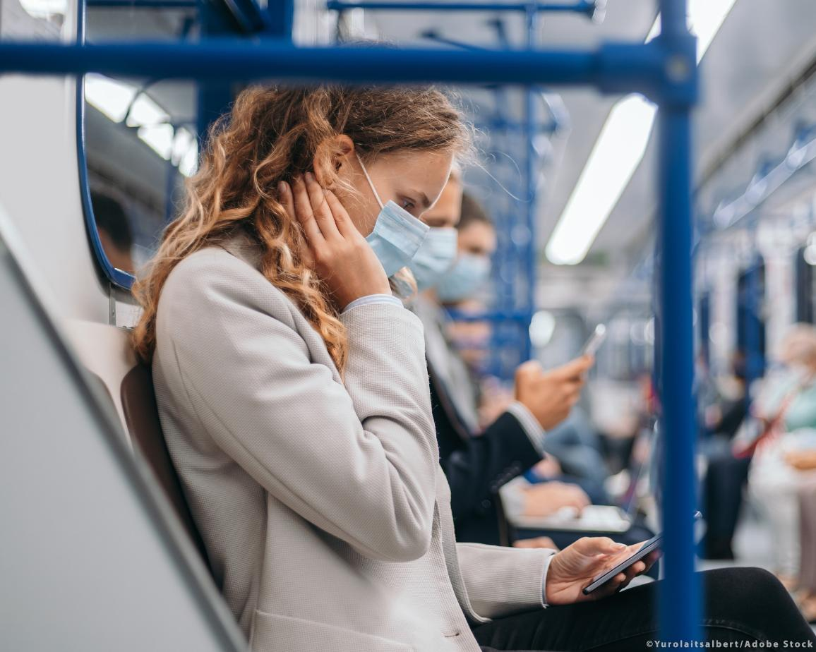 Covid-19 tracing apps: passengers in protective masks using a mobile phone ©AdobeStock/Yurolaitsalbert
