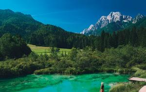Snow covered mountain. Forest. Green lake. Woman enjoying freedom on nature outdoors.
