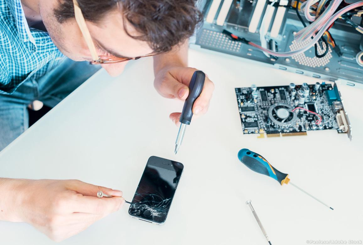 Professional repairman fixing a broken phone in a service center. ©AdobeStock/Paolese