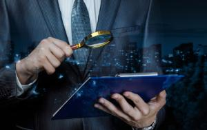 Photo of a man holding a magnifying glass over documents.