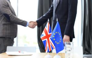 Hand shaking between two persons in front of EU and UK flags