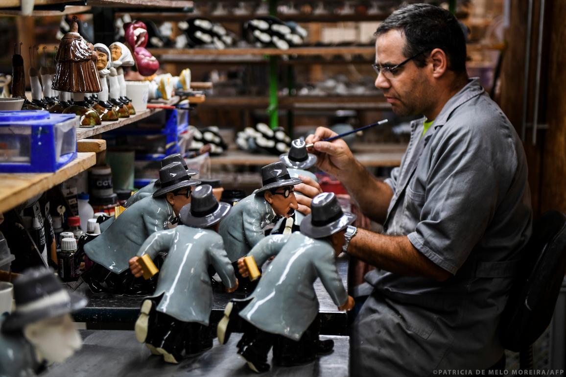 A worker of a Portuguese small enterprises paints a ceramic piece depicting writer Fernando Pessoa.  ©PATRICIA DE MELO MOREIRA/AFP