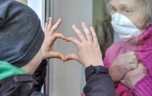 A boy is making a heart-shaped sign in front of lady with a mask behind a glass door