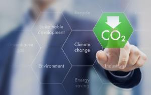 """Image idea is """"Lets reduce the CO2 emissions"""". It shows a blurred man figure pointing finger at green hexagon, which has CO2 sign topped with downwards arrow inside"""