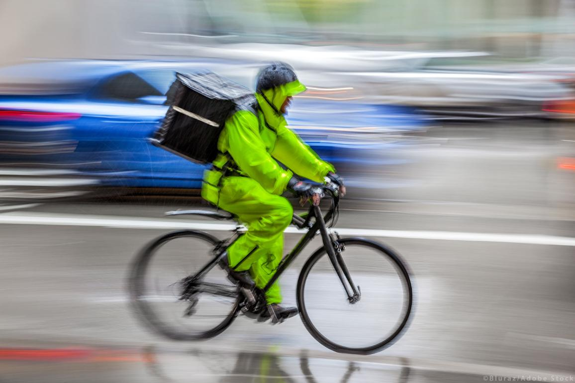 In-work poverty: a gig economy worker riding a bike to make a delivery