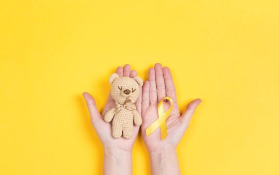 Teddybear, yellow ribbon and hands on a background of yellow, the international colour for childhood cancer