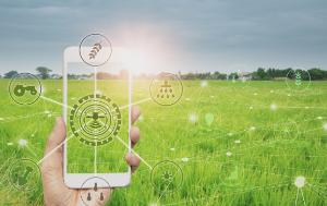 Transparent smartphone surrounded by logos such as a tractor, water drops, wheat, drone, with a green cultivated field in the background