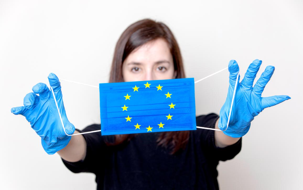 Young woman wearing gloves and holding a face mask with the European symbol