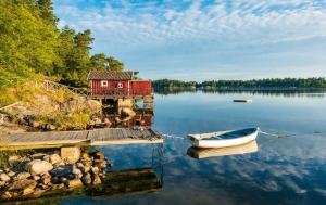 Small wooden red house at a Swedish lake with a row boat.