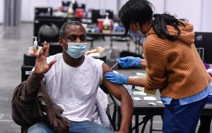 Afro-American man getting vaccinated by a woman.