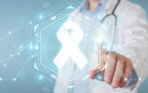A doctor in a white coat, pointing at a digital screen, white cancer ribbon