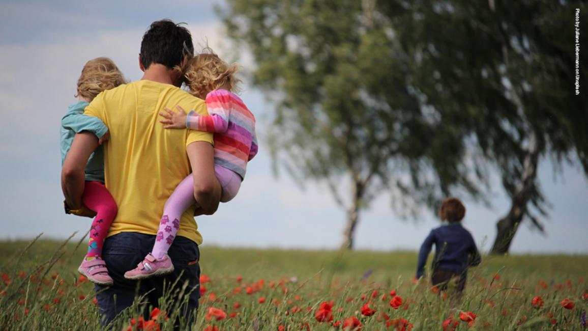 Father with children walking in a field