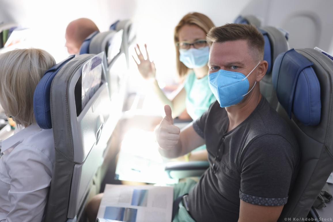 Man and woman in medical protective masks on plane. ©H_Ko/AdobeStock