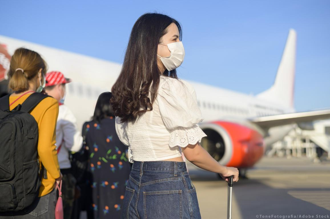 Un giovane viaggiatrice che indossa una maschera protettiva  si prepara a salire su un aereo pronto al decollo. ©AdobeStock/ToneFotografia