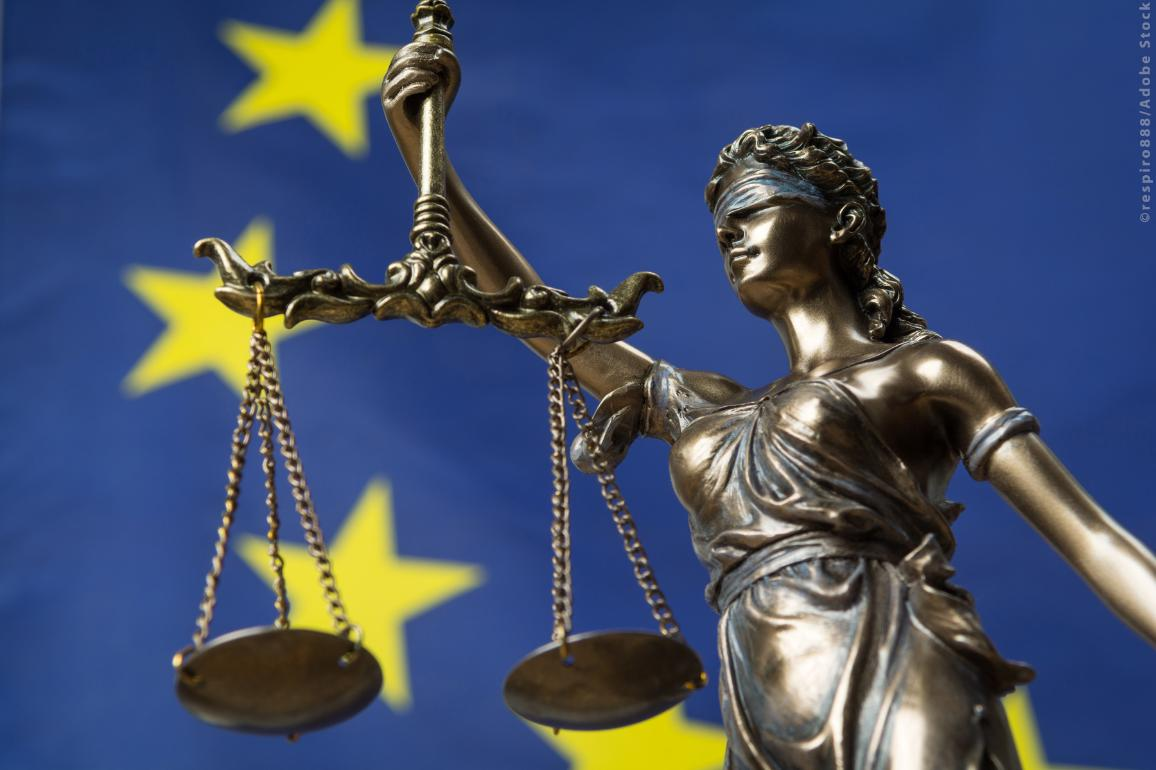Statue of the blindfolded goddess of justice with the European flag as background