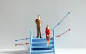 The concept of gender gap. A miniature man and a miniature woman standing at different heights on the stairs.